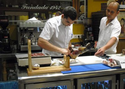 On our tapas tours, cutting acorn-fed Iberian ham in a tapas bar