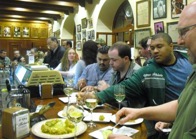 On our tapas tour, a group of people eating seafood tapas in a bar in Seville
