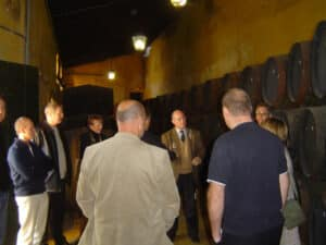 A group of people in a winery with one person explaining