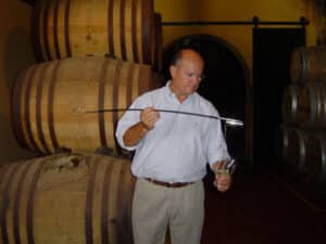 A man using a venencia to pour brandy from Jerez
