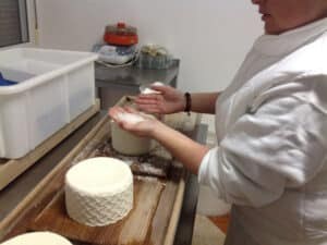 A woman is putting salt on fresh cheese