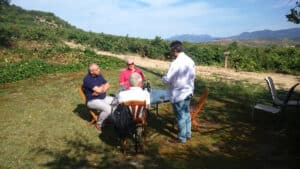On our customised tours, a group sitting outside next to a vineyard tasting wine